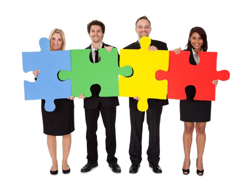 14313976 - group of business people assembling jigsaw puzzle  isolated on white